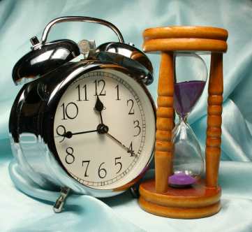 Alarm-clock and sandglass on blue background